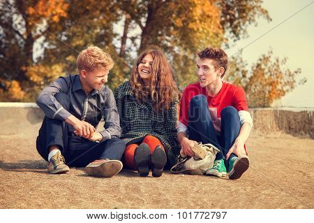 Three Teenage Friends Have A Fun Time In Golden Autumn Day