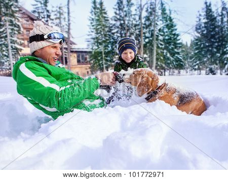 Father And Little Son Playing With Their Beagle In Deep Snow
