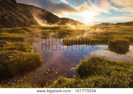 Sunrise Park Landmannalaugar. White nights in Iceland. Above the source of thermal water steam rises