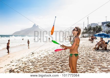 RIO DE JANEIRO, BRAZIL - APRIL 24, 2015: Brazilian girl juggles with cones toward Two Brothers Mountain at Ipanema Beach on April 24, 2015, Rio de Janeiro. Brazil.