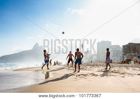 RIO DE JANEIRO, BRAZIL - APRIL 24, 2015: Carioca Brazilians playing football during sunset on the Ipanema Beach on April 24, 2015, Rio de Janeiro. Brazil.