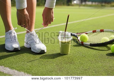 Tennis player tying shoes