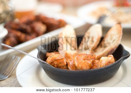 Barbecue shrimp with bread in a small cast iron skillet.