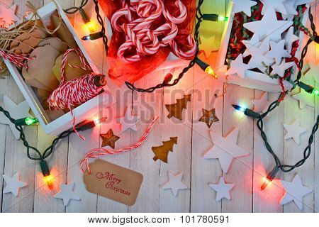High angle shot of items for wrapping Christmas presents with colorful holiday lights.