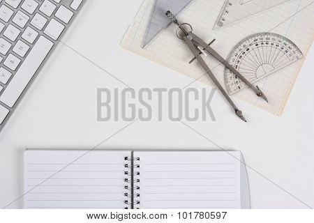 Overhead mock up of a white drafting table with computer keyboard, compass, protractor and angle open notebook and graph paper. Horizontal format with copy space.