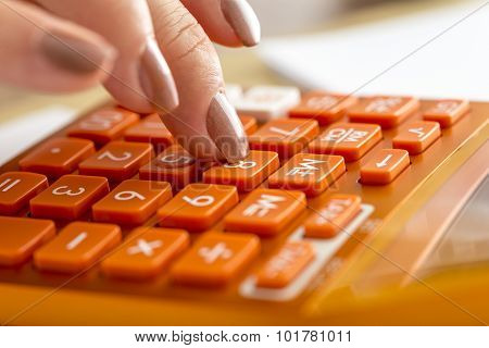 Closeup Of Female Accountant Pressing Number Eight On Orange Desktop Calculator