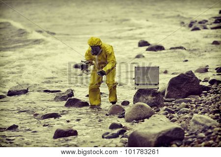 specialist in protective suit taking sample of water to container on rocky shore