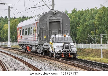 Auto Car On The Railway Wheels Pulls Railway Carriage.
