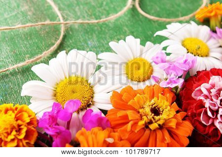Fresh colorful flowers on wooden table, closeup