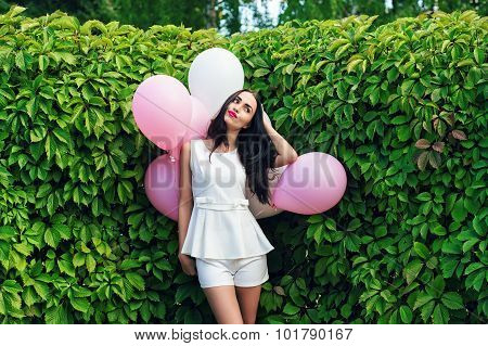charming girl with balloons in green hedgerow