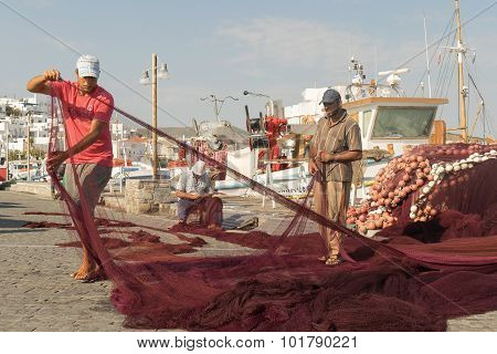 Paros, Greece 15 August 2015. Fishermen on their everyday work repairing the fishing net at Paros is