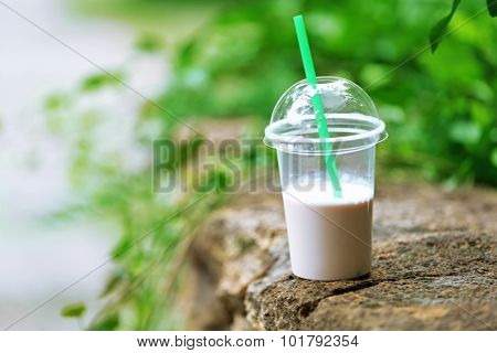 Plastic cup of milkshake on green background, outdoors