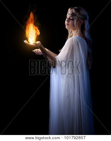 Young elven girl with fire isolated on black