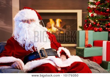 Portrait Of Santa Claus Sitting By Fireplace