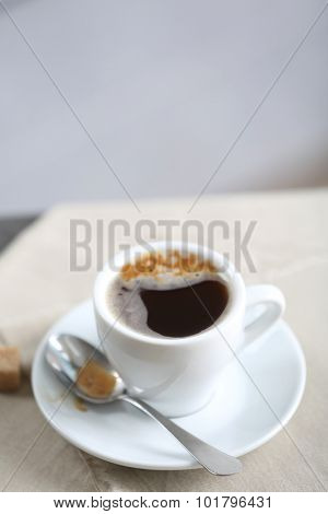 Cup of flavored coffee on table with napkin, closeup
