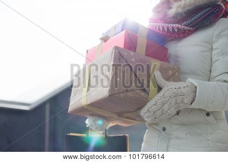 Midsection of woman carrying stacked gifts during winter by window