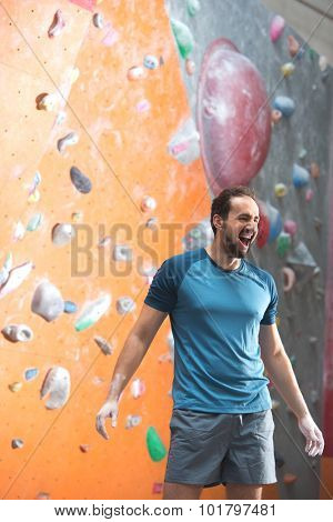 Dedicated man shouting by climbing wall in gym