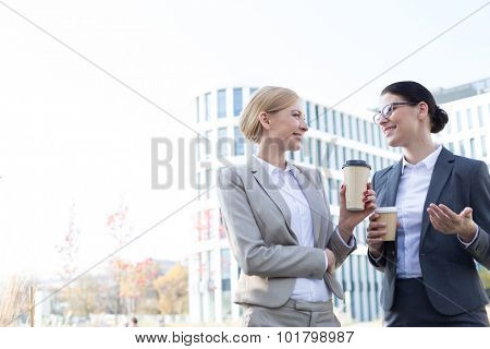 Happy businesswomen conversing while holding disposable cups outside office building