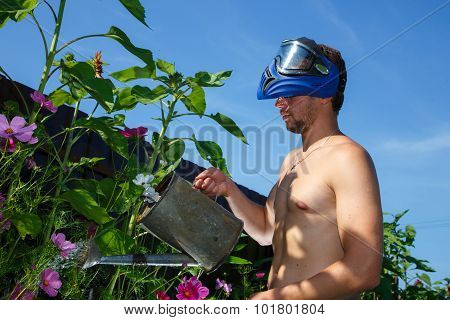 Brutal Man In Paintball Mask Watering Flowers