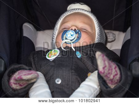 Little Boy With Dummy Sleeping In Baby Carriage