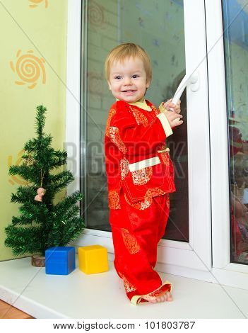 Baby Boy In Chinese New Year Costume Stands On The Window Sill