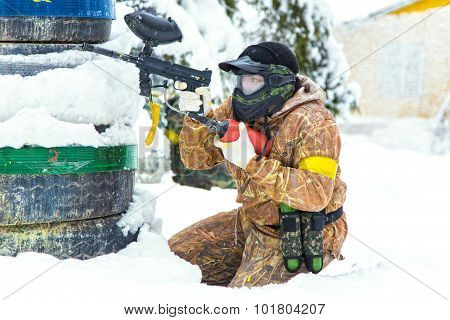 Extreme Paintball Player Aiming Behind Tyres On Snow