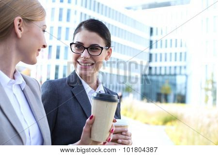 Happy businesswomen conversing while holding disposable cups outdoors