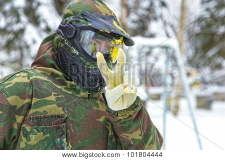 Closeup Of Paintball Player In Mask With Paint Splash Showing Peace Sign