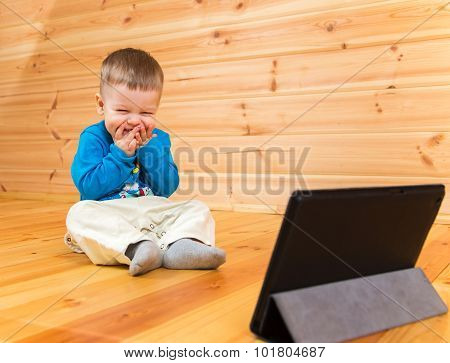 Very Pleased Little Boy Enjoying Watching His Tablet Computer