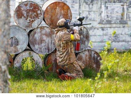 Paintball Sportsman In Ambush Behind Rusty Barrels