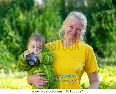 Baby Boy Drinks Water From His Bottle On Granny's Hands