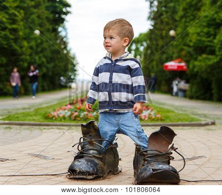 Puzzled Two Years Old Boy Standing In Giant Boots