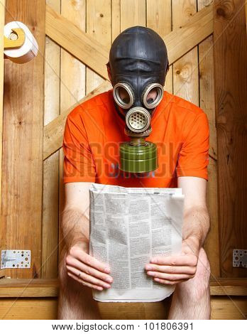Man In Gas-mask Sitting In Toilet With Newspaper