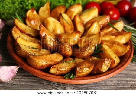 Baked potato wedges on wooden table, closeup