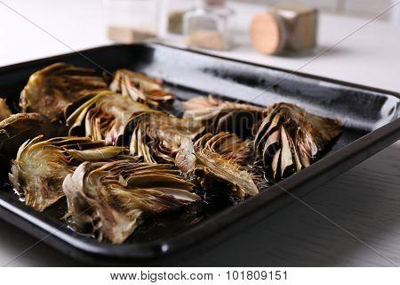 Roasted artichokes on pan, on kitchen table background