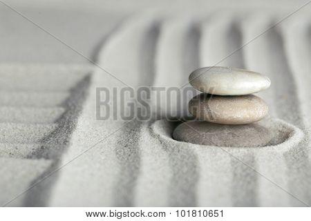 Zen garden with stones on sand background
