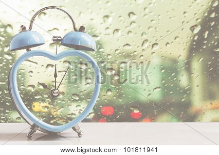 retro clock over rain drop on window background,