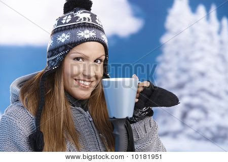 Nice Girl Drinking Hot Tea In Ski Resort Smiling