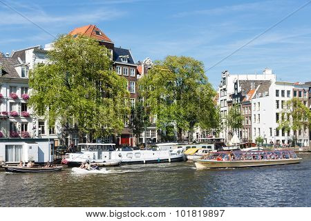 Canal With Cruise Ship Downtown In Amsterdam, The Netherlands