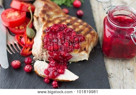 Grilled meat with cranberry sauce. Selective focus