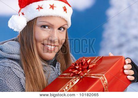 Frau in Nikolausmütze mit Weihnachtsgeschenk