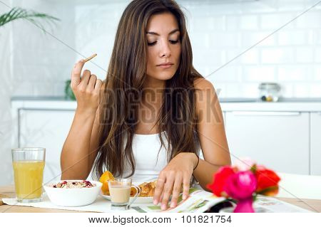 Beautiful Young Woman Reading The News And Enjoying Breakfast.