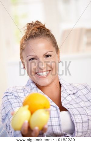Portrait Of Young Woman Holding Lemons In Hand