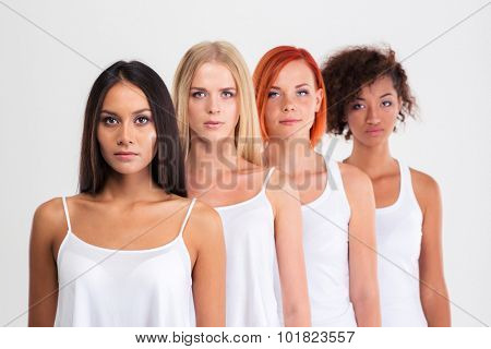 Portrait of a four serious women with colourful hair standing in a raw isolated on a white background