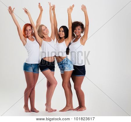 Full length portrait of a four multi etchnic girls standing with arms raised up isolated on a white background