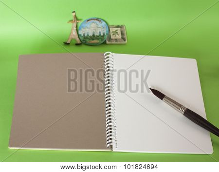 Open spiral-bound sketchbook with blank pages of brown and white paper, with place for text