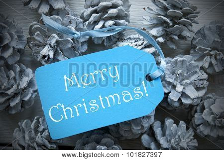 Light Blue Label On Fir Cones With Merry Christmas