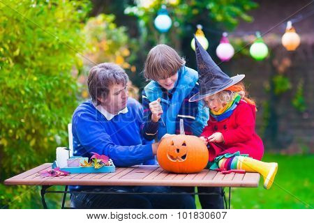 Family Carving Pumpkin At Halloween