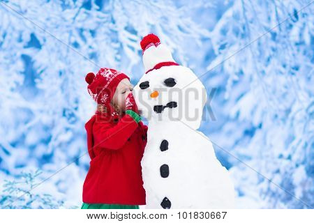 Little Girl Building A Snow Man