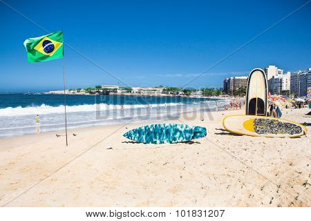Brazilian flag and surfboard  at Copacabana Beach in Rio de Janeiro. Brazil.